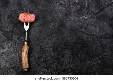 Slices of roast beef on meat fork on dark black background with copy space. Top view.