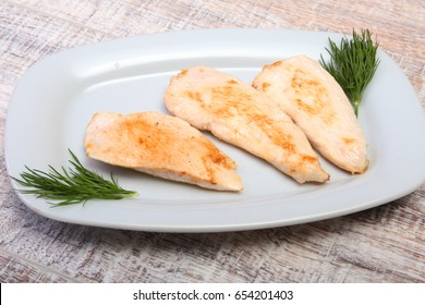 Slices of roasted chicken breast and tomato on white plate