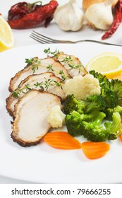 Slices of roasted pork meat served with cooked vegetables