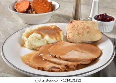 Slices of roasted turkey breast smothered in gravy with mashed potatoes and candied yams.