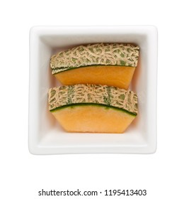 Slices of rock melon in a square bowl isolated on white background