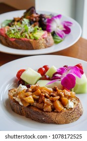 Slices of Rustic Bread Topped with Spiced Apples, Cheese, Walnuts, Avocado Served with Fresh Fruit