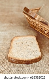 slices of rye bread and a wicker dish on burlap surface