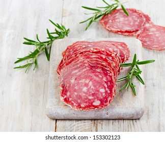 Slices of salami on wooden table. Selective focus