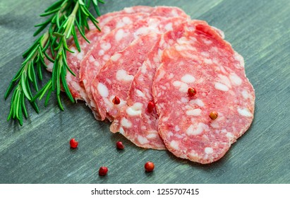 slices of salami with red and black pepper on wood