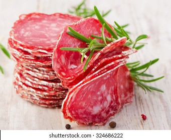 Slices of salami sausage on wooden table. Selective focus
