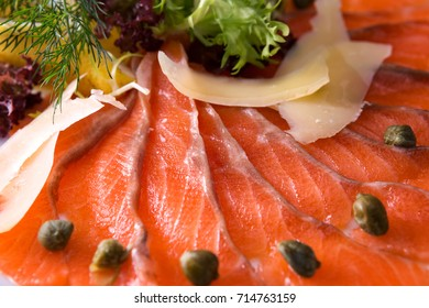 slices of salmon with cheese and greens