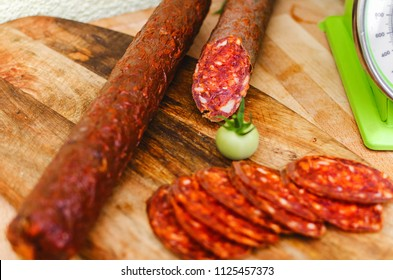 slices of sausages on a wooden board on which the green tomato is in the background is a measuring scale