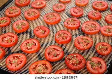 Slices of seasoned tomatoes on a drying rack for preserving