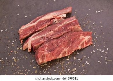 Slices of short rib beef strips with spices sprinkled over them on a black background