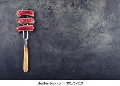 Slices of sirloin beef steak on fork.
