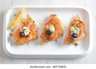 slices of smoked salmon with olives and butter on fried