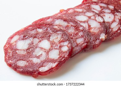 Slices of smoked sausage close up on white background