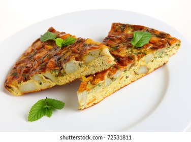 Slices of Spanish omelet or tortilla de patatas on a white plate, garnished with mint leaves