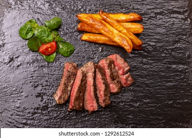 slices of steak with fries on slate