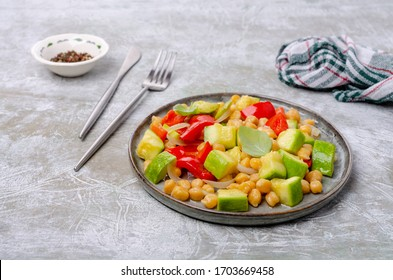 Slices of stewed vegetables with chickpeas in a dish on a slate background. Selective focus.
