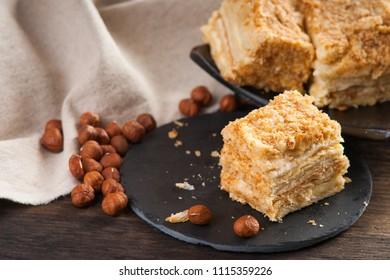 Slices of sweet classic layered cake Napoleon and hazelnuts