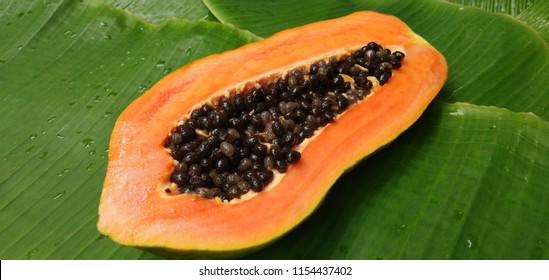 Slices of sweet papaya on banana leaves background.