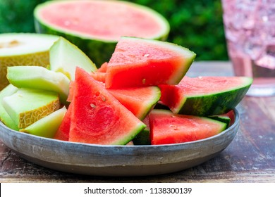 Slices of sweet, refreshing watermelon and honeydew melon on a garden table. Summer outdoor eating.