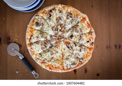 slices of tasty authentic homemade cheese pizza on wooden plate and table in home environment