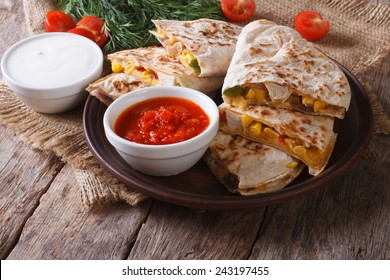 Slices of tasty Mexican quesadilla on a plate and sauces closeup. horizontal