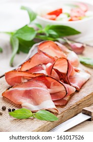 Slices of tasty spanish ham on board