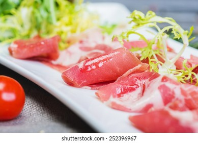 Slices of tasty traditional spanish ham iberico on a white plate with herbs and tomatoes