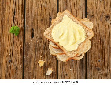 Slices of toast bread  with butter on wooden table