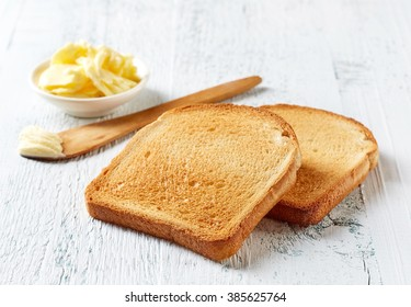 Slices of toast bread and butter on wooden table