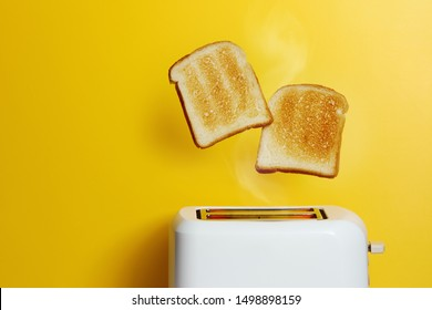 Photo of Slices of toast jumping out of the toaster against yellow background.