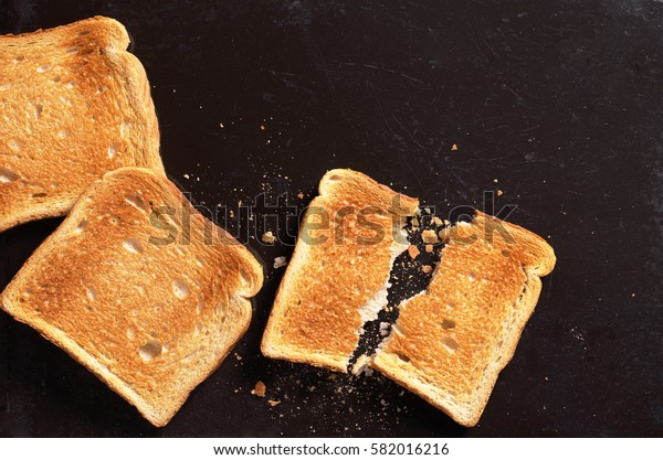 Slices of toasted bread on black background, top view
