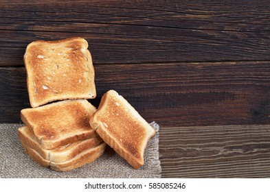 Slices of toasted bread on the dark wooden table, Space for text