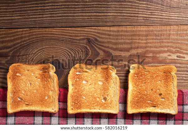 Slices of toasted bread on rustic wooden table, top view. Space for text