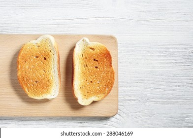 Slices of toasted bread on wooden board, top view