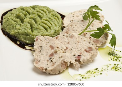 Slices of turkey roll with mashed peas as side dish