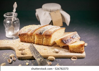 Slices of vanilla cake with strawberry jam and pistachios on a dark background