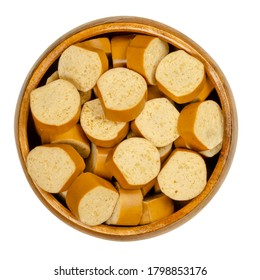 Slices of vegan Vienna sausages in a wooden bowl. Parboiled sausages, made of tofu, smoked at low temperature. Also called Wiener or Frankfurter Wuerstl. Close-up, from above, over white, food photo.