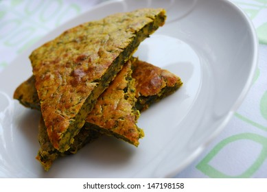 Slices of vegetarian chickpeas cake with herbs in a white dish