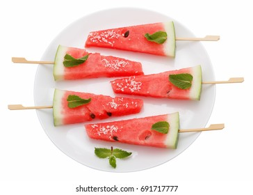 Slices of watermelon with stick on white plate isolated on white background. It looks like ice cream. Decorated with mint leaves and coconut.