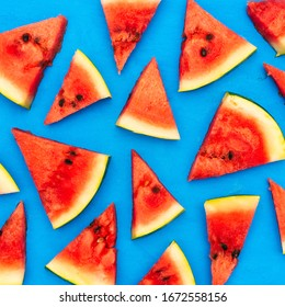 Slices of a watermelon triangular in shape on a blue background. Summer time concept.