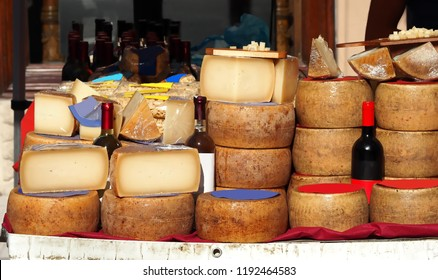 Slices and wheels of Pecorino cheese together with bottles of Cannonau, white wine, pasta and other Sardinian typical dishes on an outdoor market  shelf