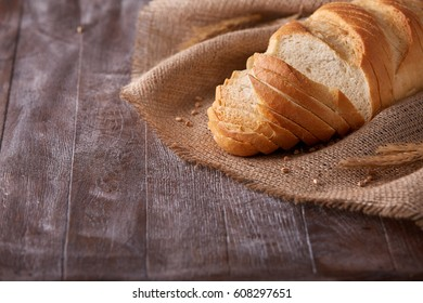 Slices of white bread on burlap on the dark wooden table, Space for text