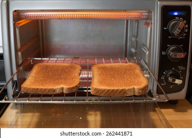 Slices of whole wheat toast on the rack of a toaster oven with open door. Shot from an eye level point of view with shallow depth of field.