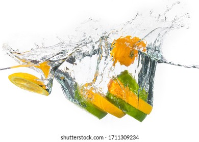 Slices of yellow and green lemon splashing on water in a white background