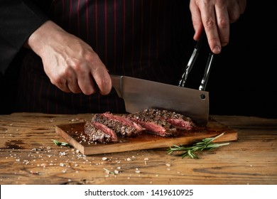 Slicing juicy beef steak by knife in chef hands closeup. Food cooking concept. Dark black background copy space.