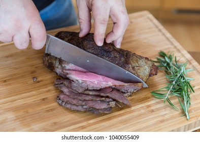 Slicing juicy Roast beaf with knife on wooden cutting board