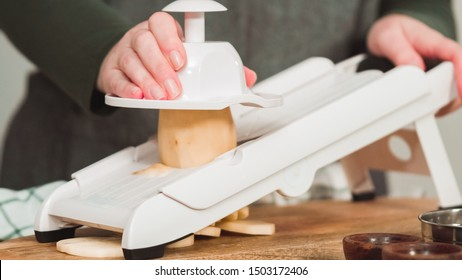 Slicing organic gold potatoes on a V-blade mandoline to prepare scalloped potatoes. - Shutterstock ID 1503172406