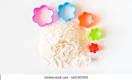 A slide of flour on a white background and a set of six bright cookie cutters in the form of a flower of different colors and sizes. Preparation for baking cookies, creativity at home top view.