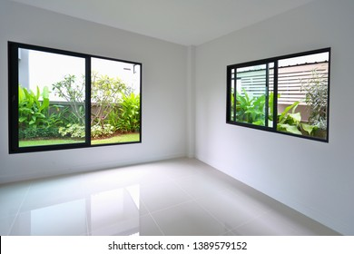 slide glass window and clean tile floor in empty room with small garden landscaping outside a new house