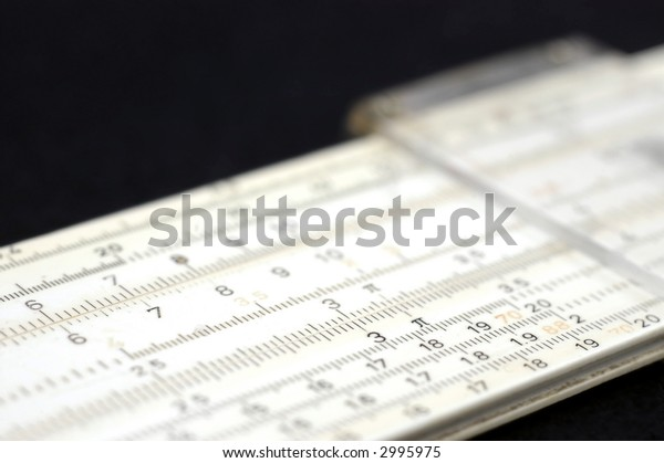 A slide rule from the sixties on a diagonal in shallow focus against black